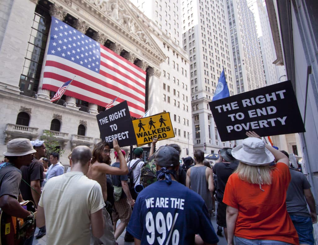 """W 2006 roku zaczęło być widać załamanie na rynku nieruchomości w USA. W 2008 roku upadł bank Lehman Brothers, a skutki kryzysu odczuwaliśmy przez kolejne lata. Na zdjęciu widać ludzi protestujących w 2012 roku w ramach ruchu """"Occupy"""". Fot. Shutterstock."""